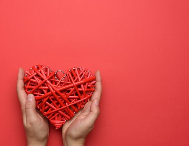 Duas mãos femininas segurando um coração de vime vermelho no conceito de vermelho, amor e bondade, copie o espaço