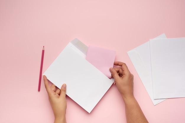 Duas mãos femininas segurando um envelope de papel branco sobre uma superfície rosa