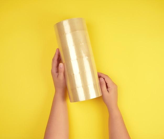 Duas mãos femininas segurando uma pilha de scotch transparente