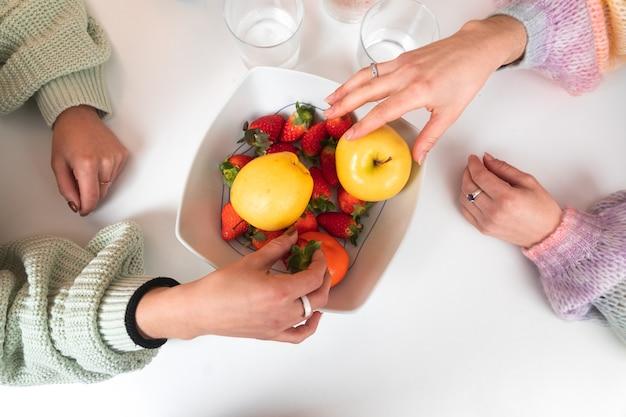 Duas mãos femininas tirando frutas de uma bola em uma mesa, vista superior