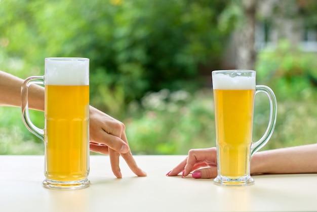Duas mãos humanas, homem e mulher com cerveja no copo. descansando homem e mulher.