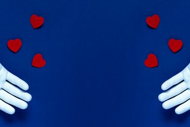 Duas mãos jogam corações vermelhos sobre um fundo azul. o conceito para o dia dos namorados