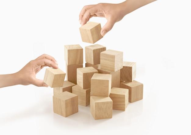 Duas mãos jogando caixa de madeira no isolado.