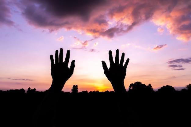 Duas mãos levantadas silhueta ao pôr do sol, conceito de halloween