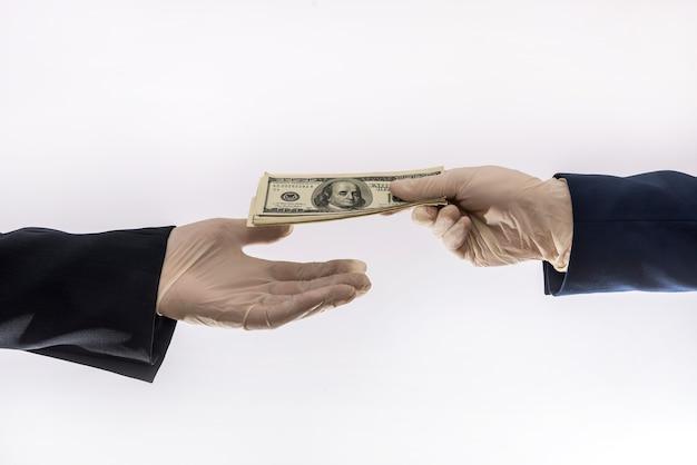Duas mãos masculinas em luvas médicas azuis com nota de 100 dólares, isoladas. conceito de corrupção ou raio na quarentena covid-19