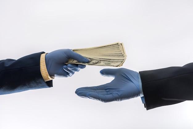 Duas mãos masculinas em luvas médicas azuis com nota de 100 dólares