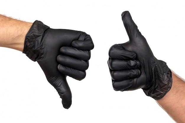 Duas mãos masculinas em luvas pretas mostram gestos com os polegares para cima e o polegar para baixo. o conceito de trabalho bem-sucedido e sem entraves