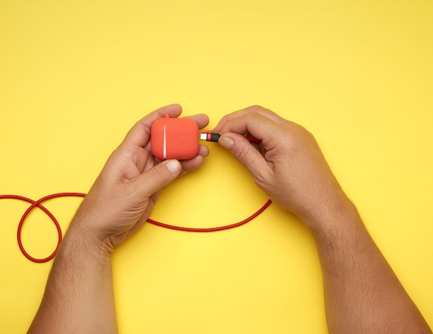 Duas mãos masculinas estão segurando um cabo e uma caixa vermelha com fones de ouvido sem fio, mesa amarela, vista superior