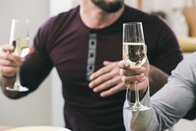 Duas mãos masculinas segurando copos de vinho branco espumante