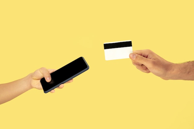 Duas mãos masculinas segurando um celular ou smartphone e um cartão de crédito