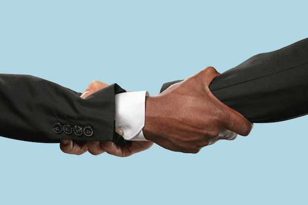 Duas mãos masculinas tremendo isoladas em azul.