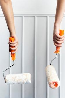 Duas mãos pintando a parede