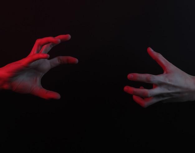 Duas mãos são atraídas uma para a outra em um fundo preto com luz de néon vermelha. conceito de halloween