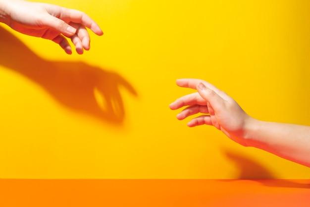 Duas mãos se alcançam com os dedos. sombras e luz forte