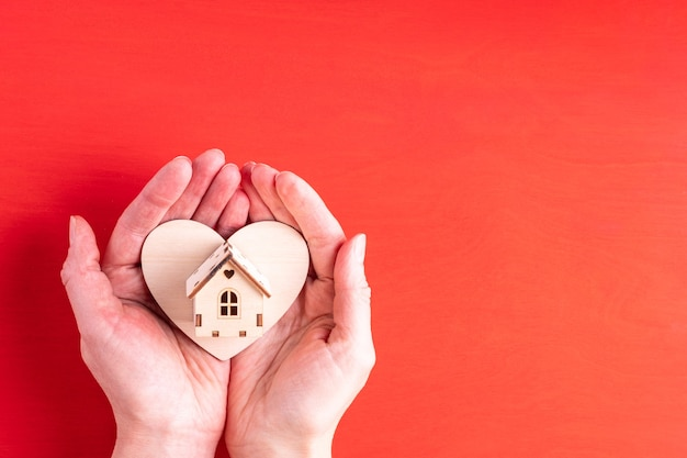 Duas mãos seguram a forma de um coração de madeira e um símbolo de casa de madeira da família, do amor e dos relacionamentos