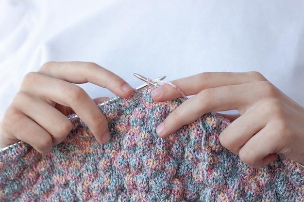 Duas mãos seguram agulhas de tricô e tricô