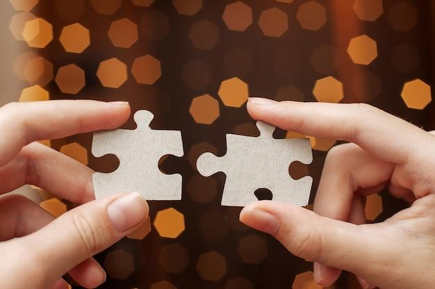 Duas mãos seguram peças do puzzle em um fundo desfocado de luzes de bokeh.