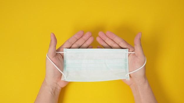 Duas mãos segurando a máscara facial ou cirúrgica para proteção contra infecção por vírus e produtos químicos. coloque um fundo amarelo.