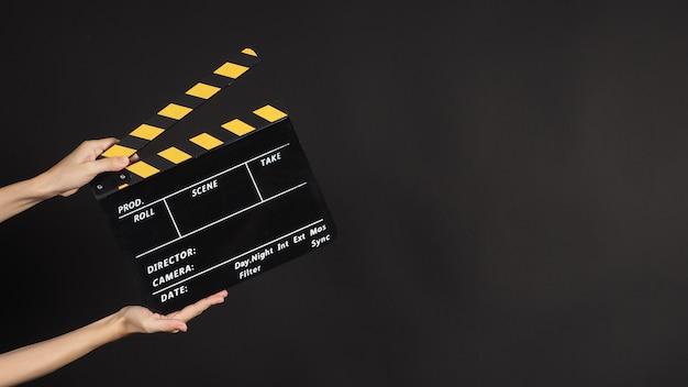 Duas mãos segurando claquete amarelo e preto ou filme ardósia uso na produção de vídeo e na indústria do cinema em fundo preto.