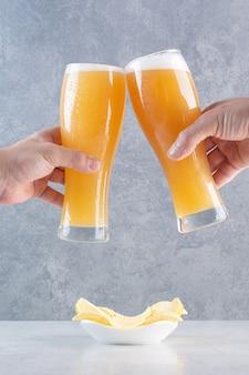 Duas mãos segurando dois copos de cerveja deliciosa.