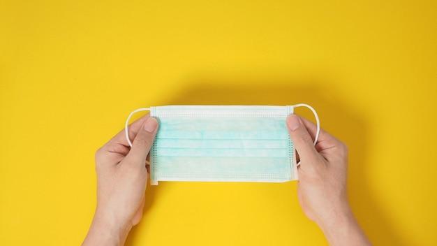 Duas mãos segurando máscara facial ou máscara cirúrgica para proteção contra infecção de vírus e produtos químicos. coloque um fundo amarelo.
