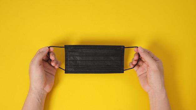 Duas mãos segurando máscara facial preta ou máscara cirúrgica para proteção contra infecção por vírus e produtos químicos. coloque um fundo amarelo.
