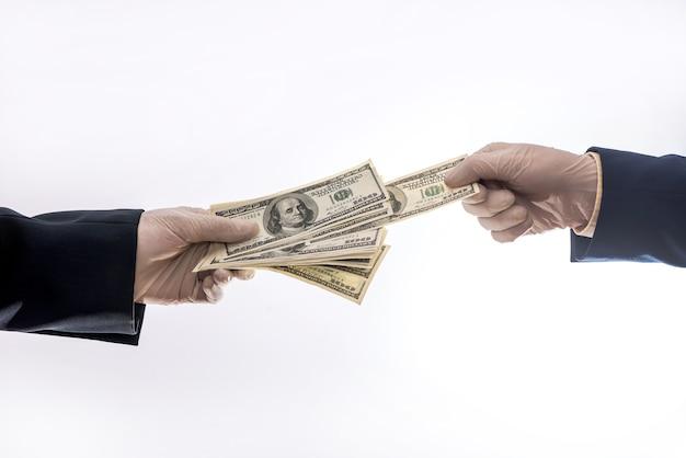 Duas mãos segurando ou dá dólares americanos em luvas médicas para proteção, período de quarentena covid 19
