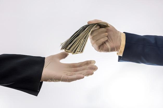 Duas mãos segurando ou dando um dólar americano em luvas médicas para proteção