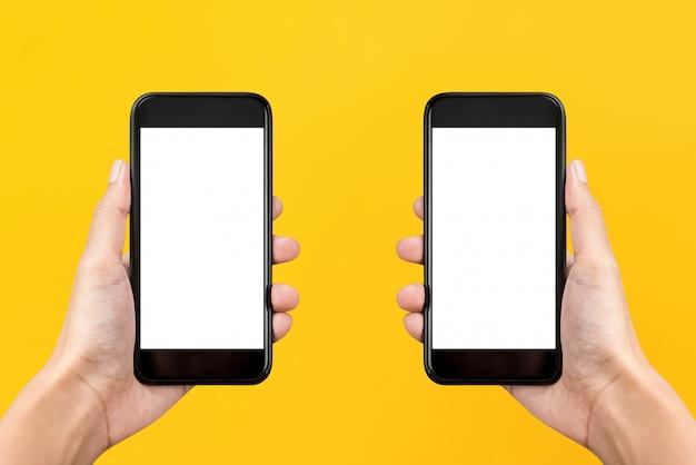 Duas mãos segurando telefones celulares com telas vazias