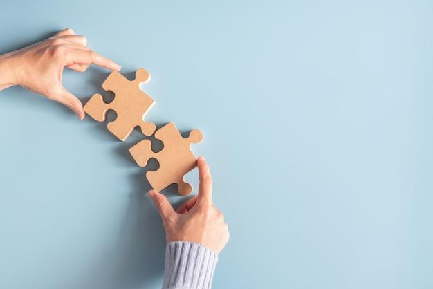 Duas mãos segurando um quebra-cabeça com trabalho em equipe