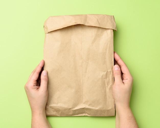 Duas mãos segurando um saco de papel kraft marrom em verde