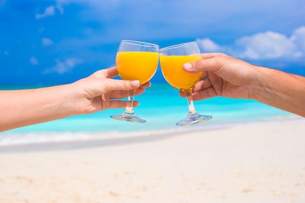 Duas mãos segurar copos com suco de laranja na praia