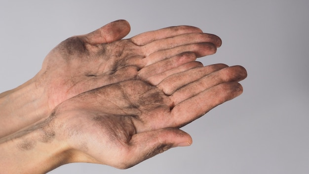 Duas mãos sujas vazias fazendo sinal de mão implorando em fundo branco.