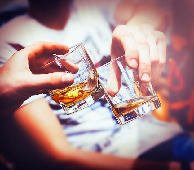 Duas mãos tilintam copos de uísque em casa, no sofá, aconchegante