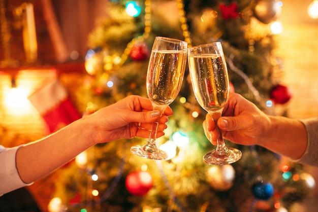 Duas mãos tilintam taças com champanhe, tradição de natal, celebração romântica.