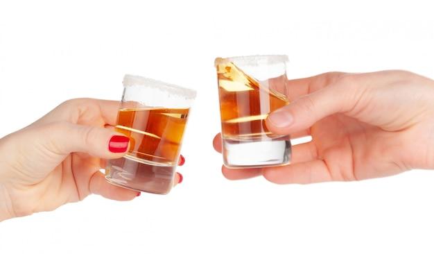 Duas mãos tinindo tiros de bebida alcoólica juntos