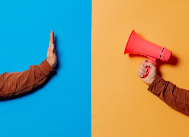Duas mãos, uma com megafone e a outra mostram o símbolo de parada em fundos azuis e amarelos