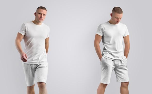 Duas maquetes para roupas de apresentação de projeto. homem caucasiano atlético atraente em uma camiseta em branco e shorts cinza de malha em um fundo branco.