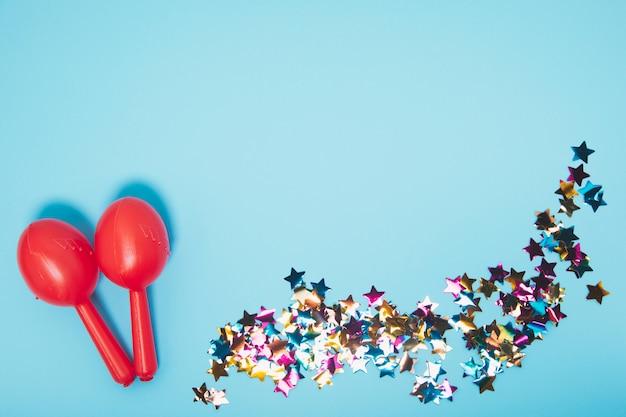 Duas maracas vermelhas com confetes coloridos da forma da estrela contra o contexto azul