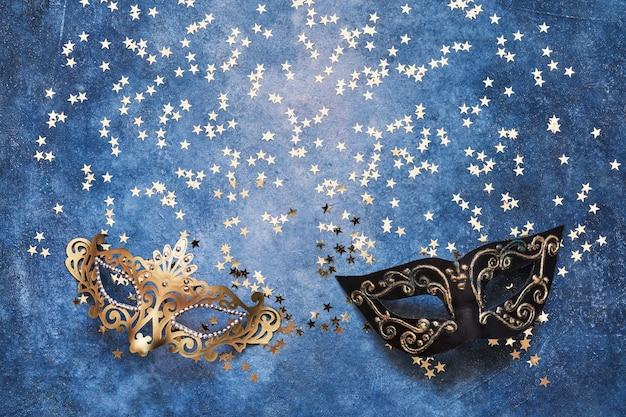 Duas máscaras de carnaval e estrelas douradas em azul. vista superior, copie o espaço. conceito de celebração da festa de carnaval.
