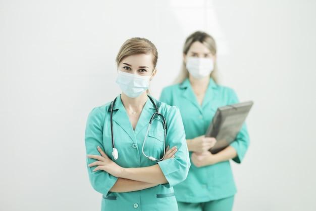 Duas médica ou enfermeira usando máscaras médicas, olhando para a câmera.