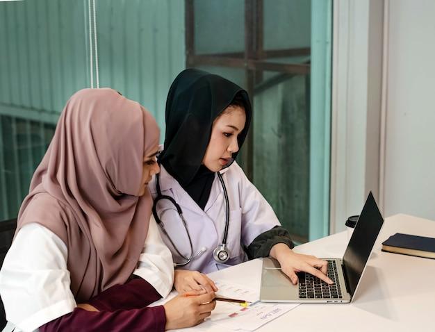 Duas médicas usando laptop para consultar sobre o tratamento do paciente, com emoção séria, tempo ocupado, trabalhando no hospital