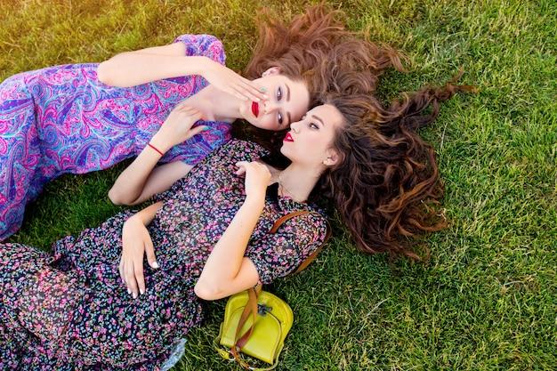 Duas melhores amigas em vestido boho colorido e cabelos cacheados, deitado na grama verde
