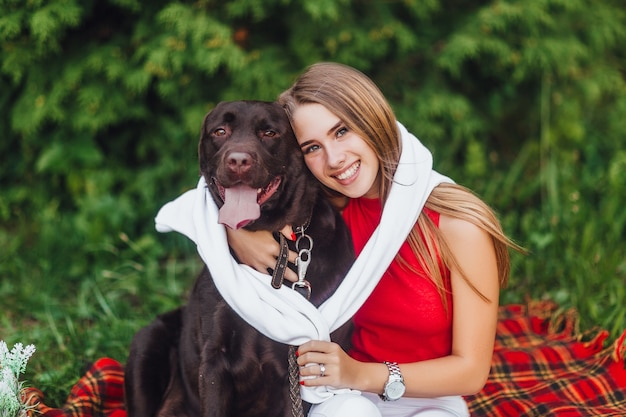 Duas melhores amigas, uma menina e seu cachorro labrador sentados no parque
