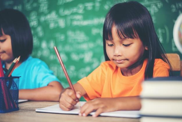Duas menina com lápis de desenho na aula na sala de aula