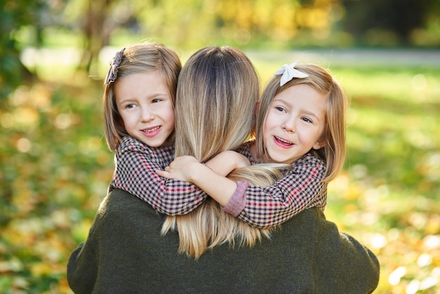 Duas meninas abraçando a mãe