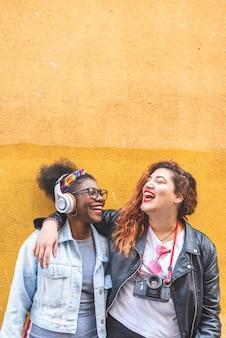 Duas meninas adolescentes em pé juntos sobre uma parede amarela