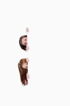 Duas meninas adolescentes tirando a cabeça de um cartaz em branco