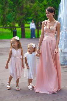 Duas meninas adoráveis com sua mãe ao ar livre no casamento