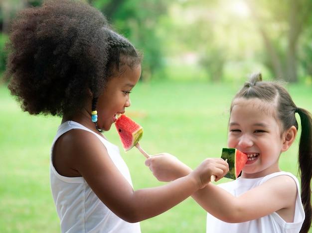 Duas meninas adoráveis de várias etnias, se divertindo comendo melancia no parque.